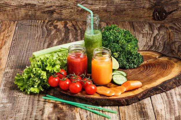 Garrafas com sucos de vegetais frescos na mesa de madeira