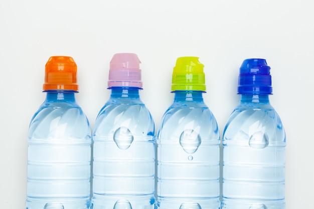 Garrafas de água plásticas com tampas de cor diferente em cima da mesa
