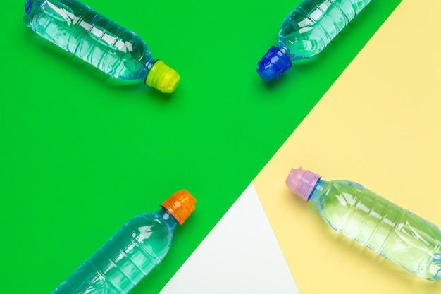 Garrafas de água plásticas com tampas de cores diferentes em cima da mesa