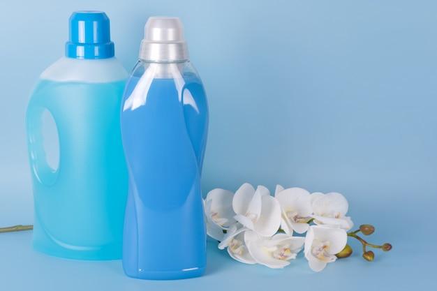 Garrafas de amaciante de detergente e tecido com flores da orquídea em fundo azul