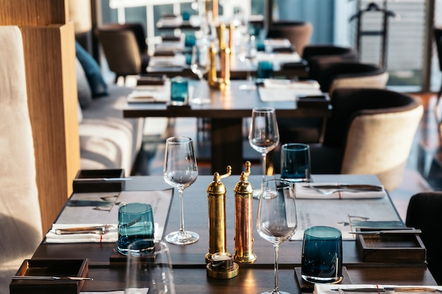 Garrafas de bronze do sal e da pimenta na tabela de madeira com a mesa de jantar do borrão no fundo.