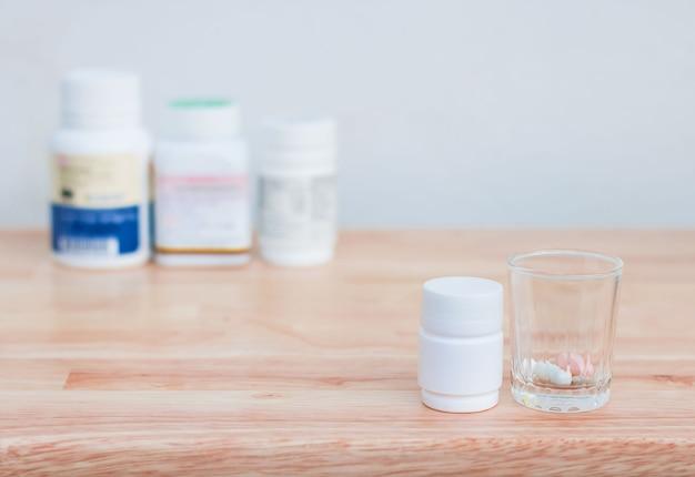 Garrafas de cápsulas e comprimidos da medicina no vidro pequeno no assoalho de madeira.