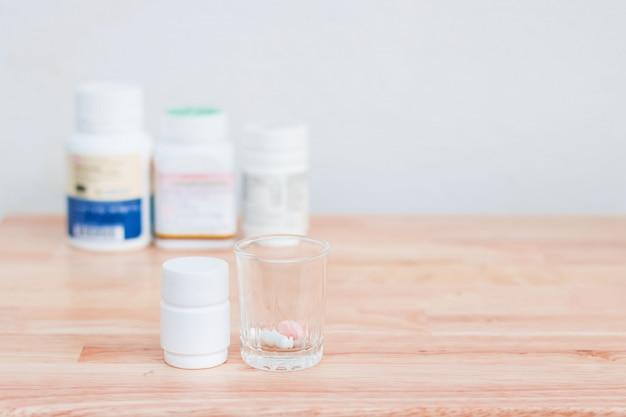 Garrafas de cápsulas e comprimidos da medicina no vidro pequeno no assoalho de madeira. Foto Premium