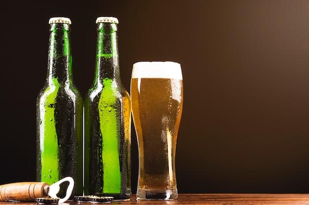 Garrafas de cerveja de close-up com um copo
