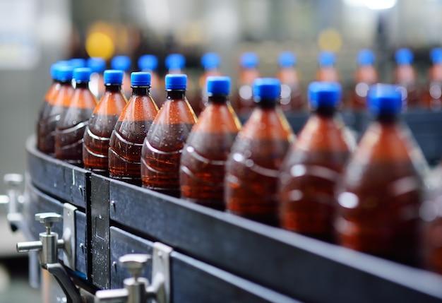 Garrafas de cerveja de plástico em uma correia transportadora no fundo de uma cervejaria