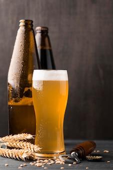 Garrafas de cerveja e copos com espuma