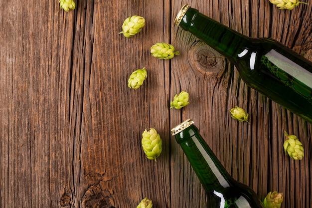 Garrafas de cerveja e lúpulo em fundo de madeira