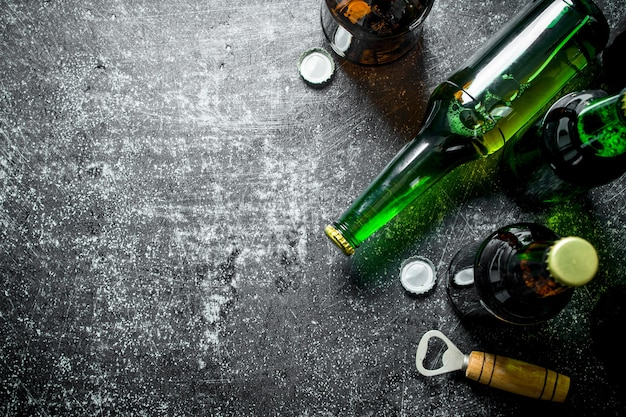 Garrafas de cerveja e um abridor. em fundo escuro rústico