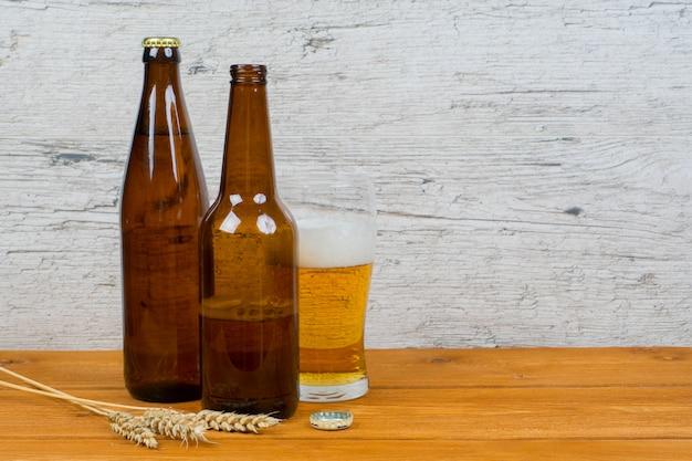 Garrafas de cerveja e um copo na mesa de pub