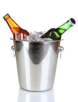 Garrafas de cerveja em balde de gelo isoladas em branco