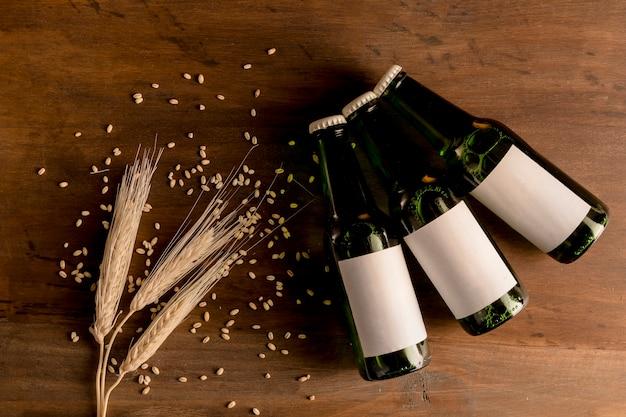 Garrafas de cerveja em etiqueta branca com espiga de trigo na mesa de madeira