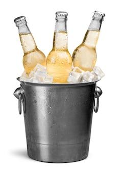Garrafas de cerveja em um balde com cubos de gelo isolados no branco