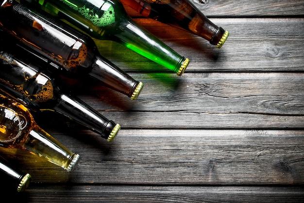 Garrafas de cerveja fechadas. em fundo preto de madeira