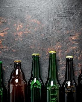 Garrafas de cerveja fechadas. em superfície rústica escura