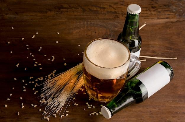 Garrafas de cerveja verde com copo de cerveja na mesa de madeira