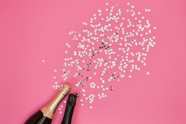 Garrafas de champanhe com confetes no fundo rosa.