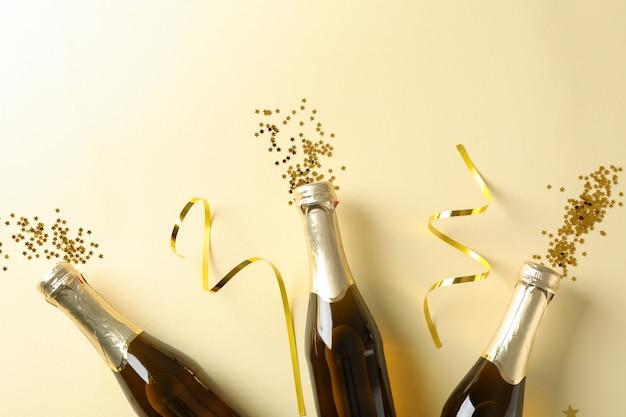 Garrafas de champanhe e glitter em bege. conceito de férias