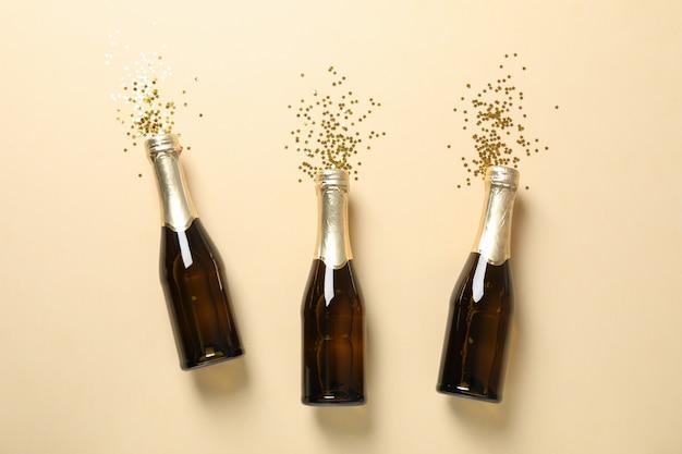 Garrafas de champanhe e glitter em bege, espaço para texto