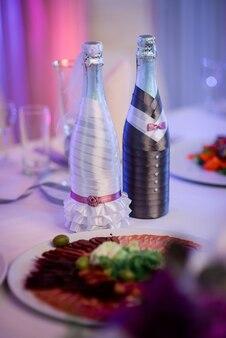 Garrafas de champanhe vestida como noiva e noivo