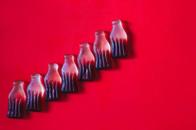 Garrafas de cola com goma de gelatina em fila, fundo de bebida e espaço de cópia