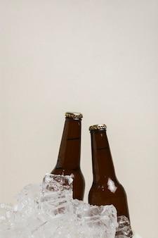 Garrafas de cópia-espaço com cerveja em cubos de gelo