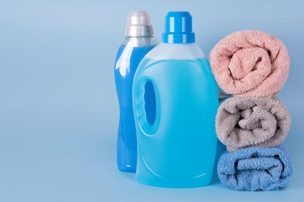 Garrafas de detergente e amaciante de roupa com toalhas limpas sobre fundo azul