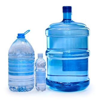 Garrafas de diferentes tamanhos com água potável, isoladas no fundo branco.