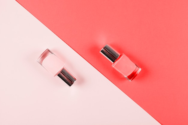 Garrafas de esmalte no pano de fundo diagonal rosa e coral