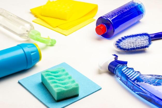 Garrafas de líquido azul, esponja, pano e escova na mesa. produtos químicos domésticos para limpar o apartamento. fundo branco. vista do topo