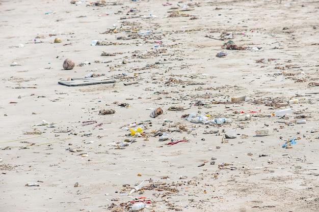 Garrafas de lixo, vidro e bolsa de plástico na praia.