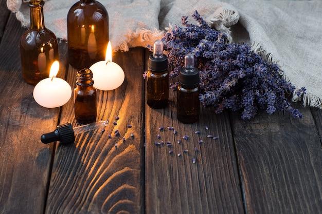 Garrafas de óleo aromático, velas e flores de lavanda