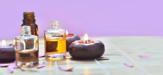 Garrafas de óleo com velas acendem sobre uma mesa no fundo rosa