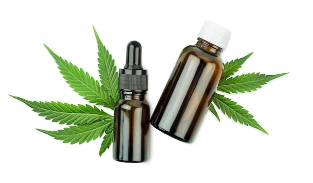 Garrafas de óleo de cânhamo e folhas de cannabis em fundo branco isolado