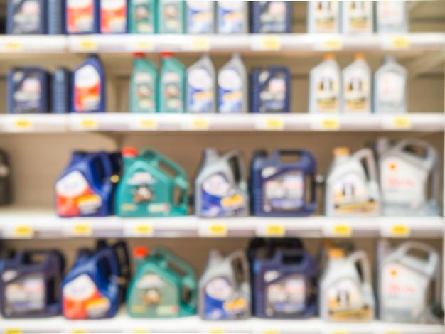 Garrafas de óleo de motor colorido turva nas prateleiras no supermercado como pano de fundo
