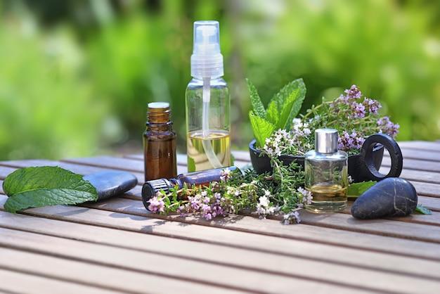 Garrafas de óleo essencial e flores de lavanda em uma mesa no jardim