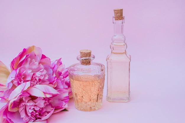 Garrafas de óleo essencial e flores sobre fundo rosa