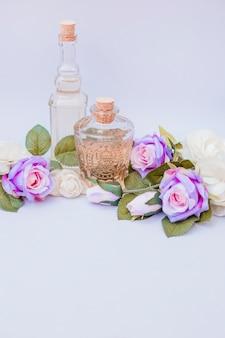 Garrafas de óleo essencial e rosas falsas em pano de fundo branco