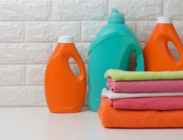 Garrafas de plástico com detergente líquido e toalhas dobradas em uma prateleira branca. interior da banheira