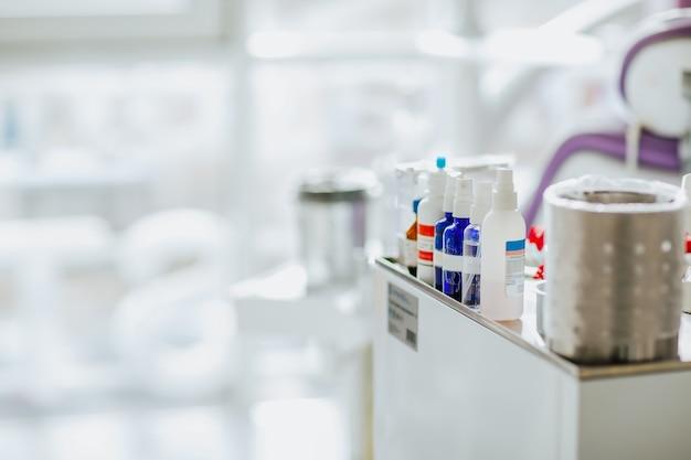 Garrafas de plástico com medicamentos odontológicos estão na mesa médica contra a grande janela