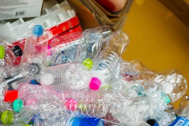 Garrafas de plástico e papelão em uma estação de reciclagem de lixo de perto