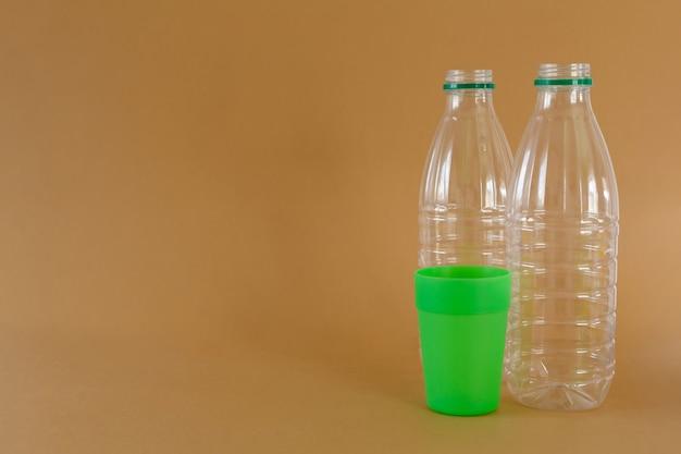 Garrafas de plástico e vidro em um fundo marrom