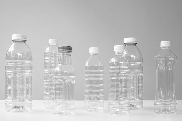 Garrafas de plástico em várias formas e tamanhos na mesa e fundo branco