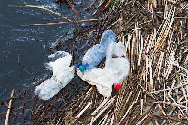 Garrafas de plástico na margem do rio, conceito para o dia da proteção dos oceanos. lixo plástico não degradável na costa.