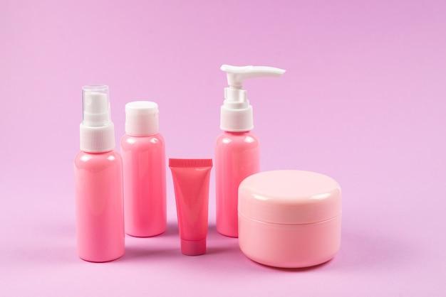 Garrafas de plástico rosa para produtos de higiene, cosméticos, produtos de higiene em uma parede rosa.