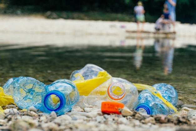 Garrafas de plástico sujas e sacos na água