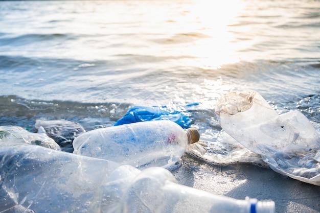 Garrafas de plástico vazias no conceito de poluição de praia, beira-mar e água