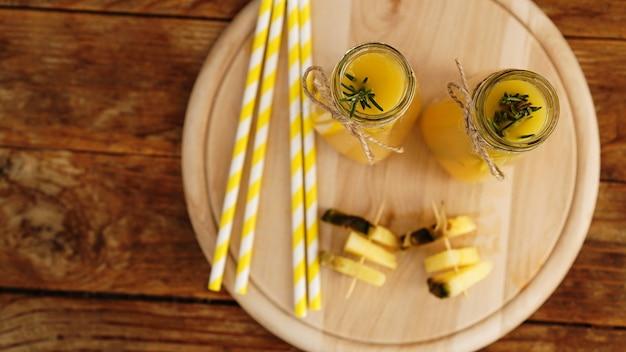 Garrafas de suco de abacaxi em uma mesa de madeira. bebida amarela e abacaxi fresco. lanche no resort. foto de verão. vista de cima