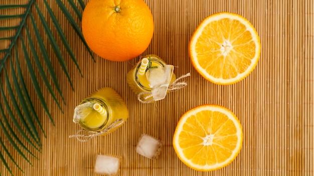 Garrafas de suco de laranja e canudos de papel. bebida gelada em um dia ensolarado