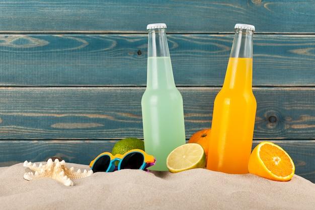 Garrafas de suco de laranja e limão na areia