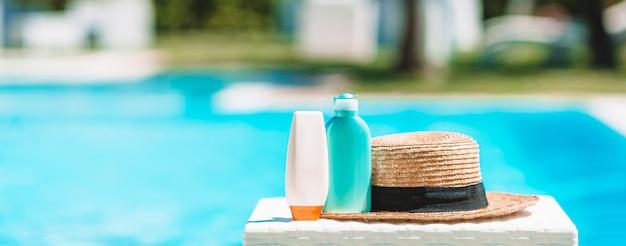 Garrafas de suncream, óculos de proteção, estrelas do mar na beira da piscina